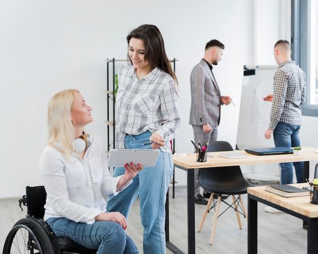 Vista lateral da mulher em cadeira de rodas, conversando com uma colega no escritório