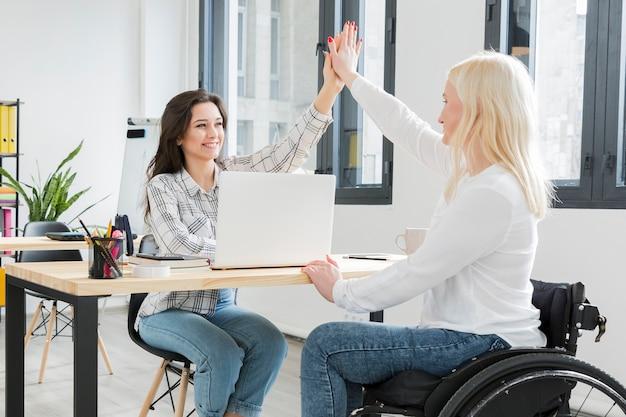 Vista lateral da mulher em cadeira de rodas cumprimentando seu colega