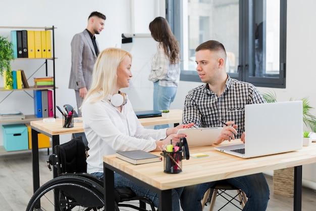 Vista lateral da mulher em cadeira de rodas, discutindo com o colega de trabalho na mesa dela