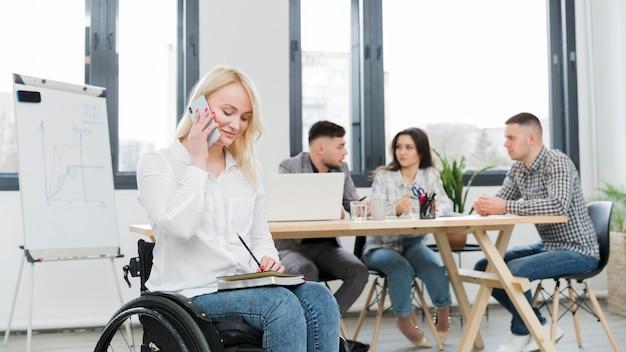 Vista lateral da mulher em cadeira de rodas, trabalhando por telefone no escritório