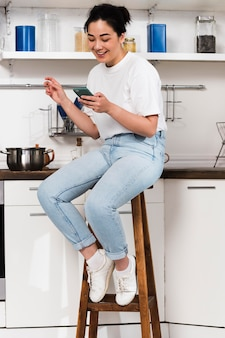 Vista lateral da mulher em casa na cozinha usando o smartphone