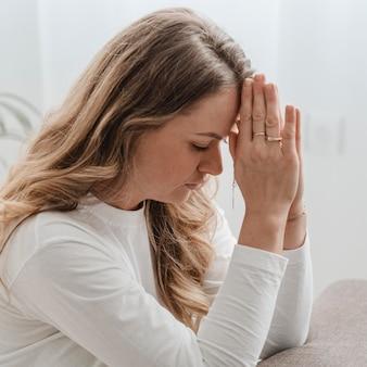 Vista lateral da mulher em casa orando