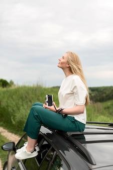 Vista lateral da mulher em cima do carro, segurando a câmera