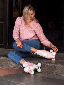 Vista lateral da mulher em jeans, verificando as rodas de patins