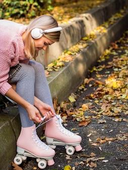 Vista lateral da mulher em patins e fones de ouvido