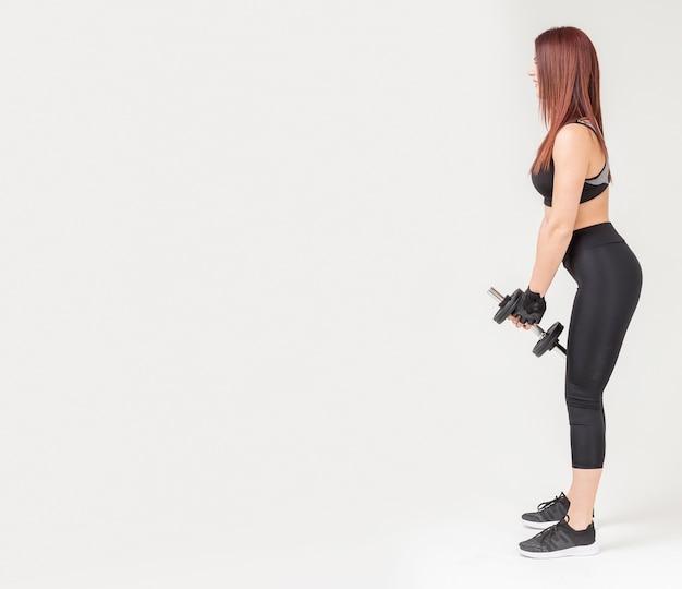 Vista lateral da mulher em trajes de ginástica, segurando o peso