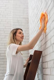 Vista lateral da mulher em uma escada de limpeza da parede de tijolos