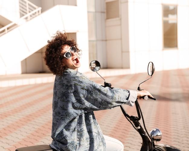 Vista lateral da mulher encaracolada grita feliz em óculos de sol posando