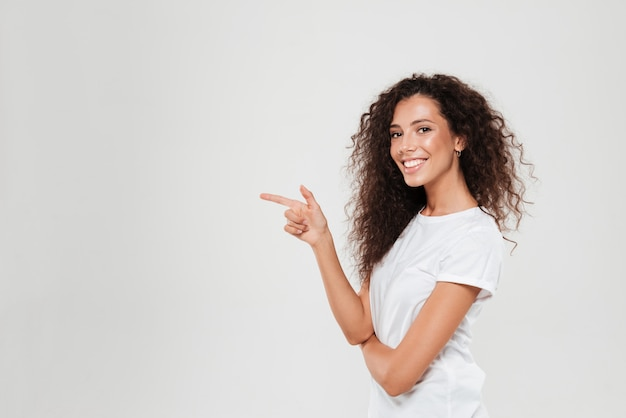 Vista lateral da mulher encaracolada sorridente apontando para fora