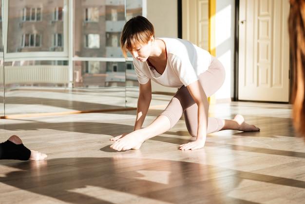 Vista lateral da mulher envolvida ioga