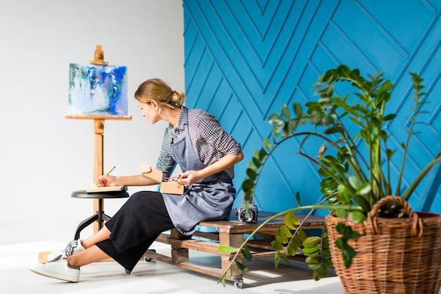 Vista lateral da mulher escrevendo e pintando