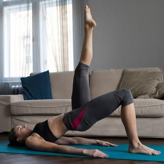 Vista lateral da mulher exercitando na esteira da ioga