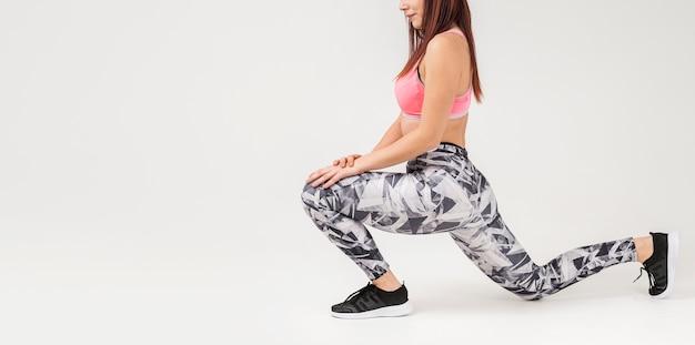 Vista lateral da mulher fazendo lunges em roupas de ginástica