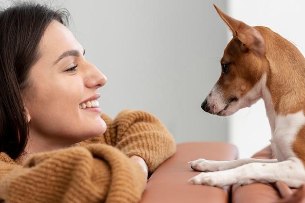 Vista lateral da mulher feliz e seu cachorro