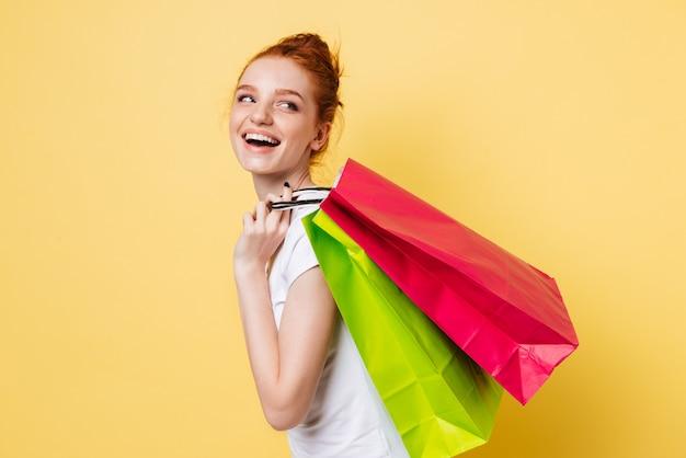 Vista lateral da mulher feliz gengibre segurando pacotes no ombro