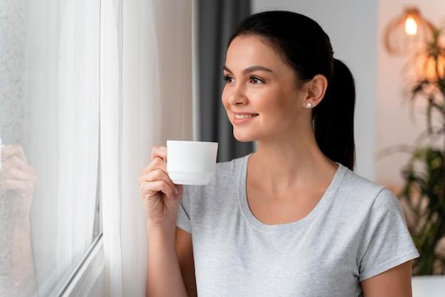 Vista lateral da mulher grávida segurando a barriga enquanto toma uma xícara de chá