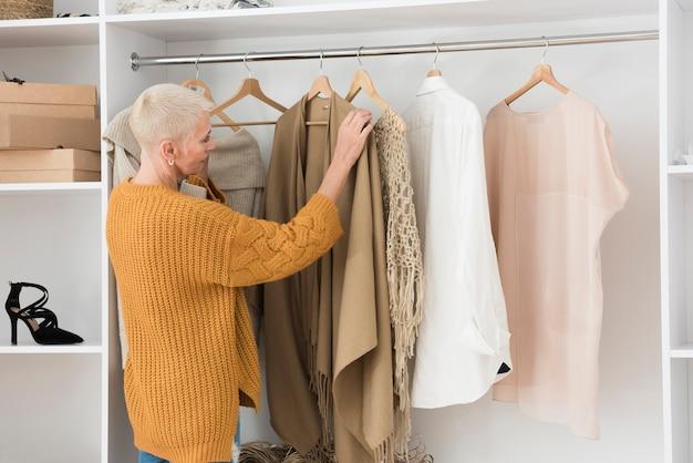 Vista lateral da mulher idosa passando por suas roupas