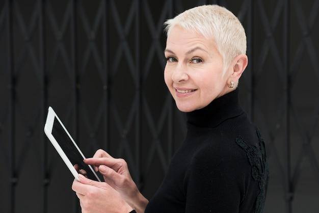 Vista lateral da mulher idosa sorridente segurando o tablet