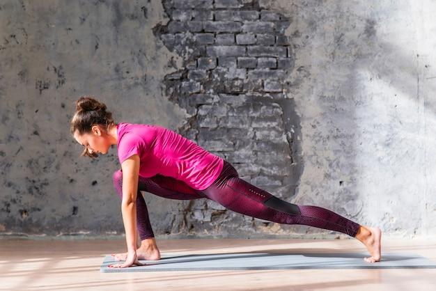 Vista lateral da mulher jovem e bonita no sportswear fazendo exercícios de alongamento