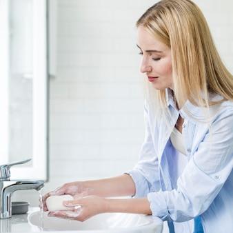 Vista lateral da mulher lavando as mãos com barra de sabão