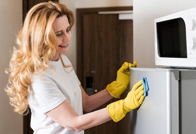 Vista lateral da mulher limpando a geladeira