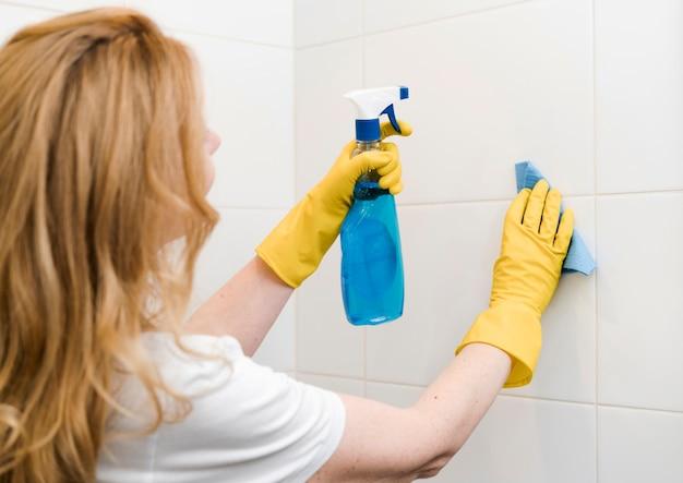 Vista lateral da mulher limpando a parede do chuveiro