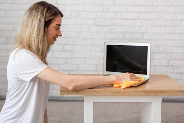 Vista lateral da mulher limpando laptop com pano