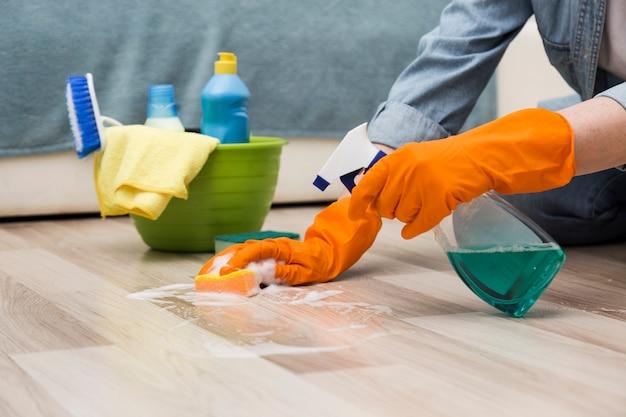 Vista lateral da mulher limpando o chão