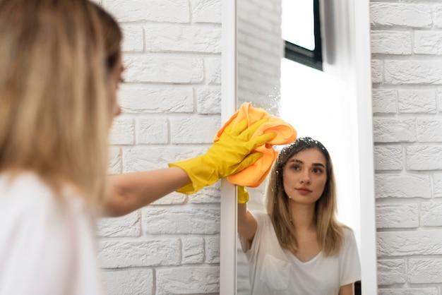 Vista lateral da mulher limpando o espelho com pano