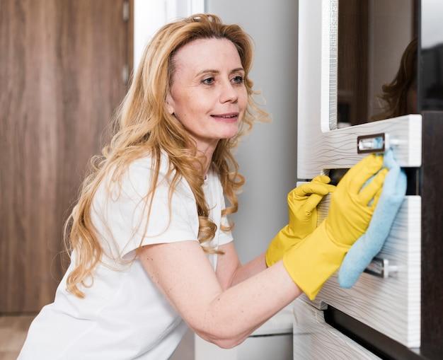 Vista lateral da mulher limpando os móveis