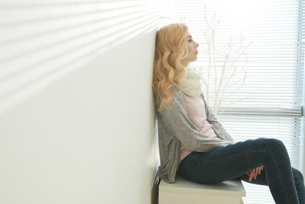 Vista lateral da mulher loira sentada exausta e ponderando em uma sala