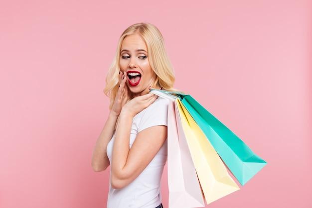 Vista lateral da mulher loira surpresa segurando pacotes no ombro e cobrindo a boca sobre rosa