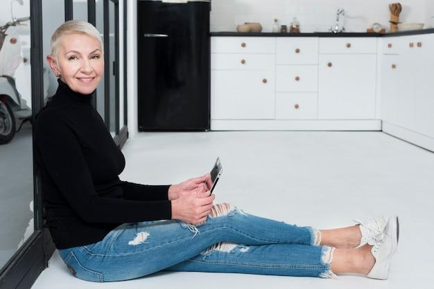 Vista lateral da mulher mais velha posando na cozinha e segurando o tablet