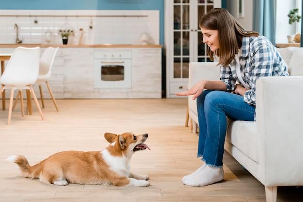Vista lateral da mulher mandando seu cachorro sentar