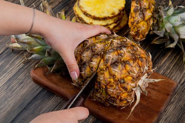 Vista lateral da mulher mãos corte abacaxi com faca na tábua com abacaxi fatiado em fundo de madeira