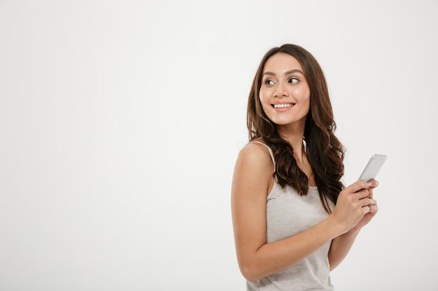 Vista lateral da mulher morena feliz segurando o smartphone e olhando para trás sobre cinza