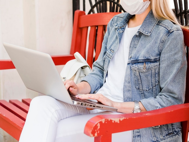 Vista lateral da mulher na cadeira usando máscara facial e trabalhando no laptop