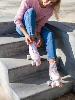 Vista lateral da mulher na escada com patins