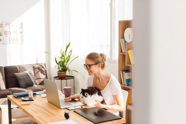 Vista lateral da mulher na mesa com gato trabalhando em casa