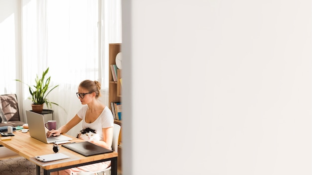 Vista lateral da mulher na mesa trabalhando em casa com espaço de cópia
