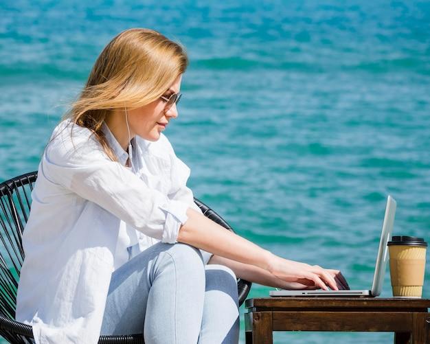 Vista lateral da mulher na praia trabalhando no laptop
