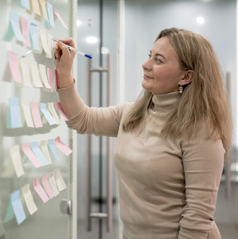 Vista lateral da mulher no escritório escrevendo sobre notas autoadesivas