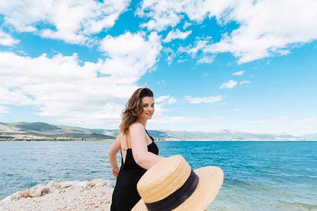 Vista lateral da mulher no oceano segurando o chapéu