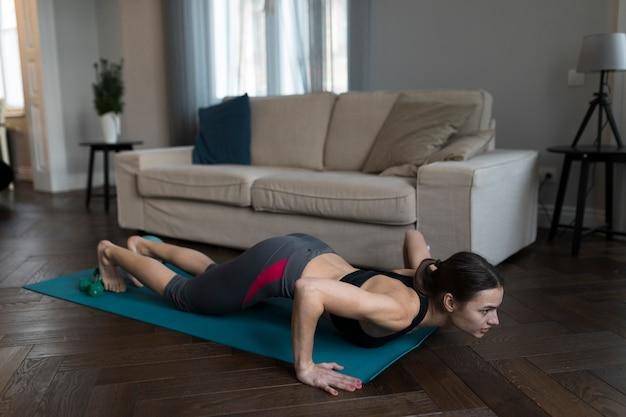Vista lateral da mulher no sportswear exercitando em casa