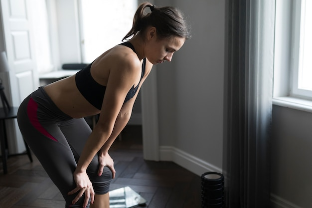 Vista lateral da mulher no sportswear relaxante após o exercício