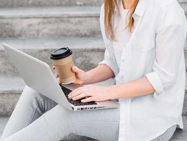 Vista lateral da mulher nos degraus com café e laptop