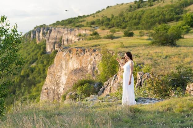 Vista lateral da mulher posando ao ar livre com montanha