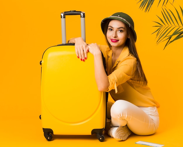 Vista lateral da mulher posando ao lado de sua bagagem