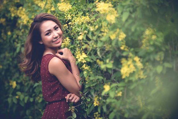 Vista lateral da mulher posando ao lado do arbusto florescendo