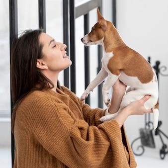 Vista lateral da mulher posando com seu cachorro